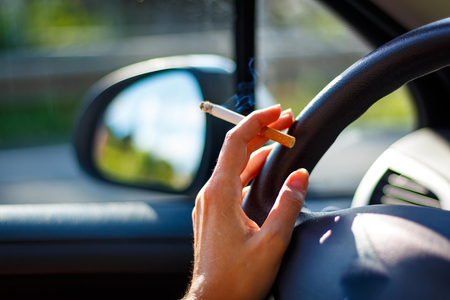 Woman smoking a cigarette at the wheel of a car.