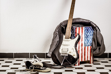 Electric guitar, leather jacket and sports shoes lying on the floor. Stock Photo