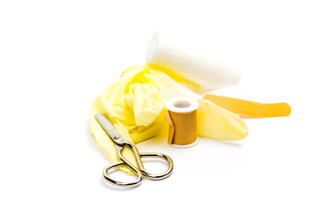 Medical gloves and bandages in front of white background.