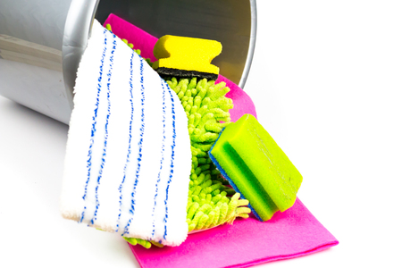 Cleaning utensils in a bucket in front of white background.