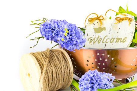 Bouquet of hyacinths in a copper bowl with a welcome sign. Stock Photo