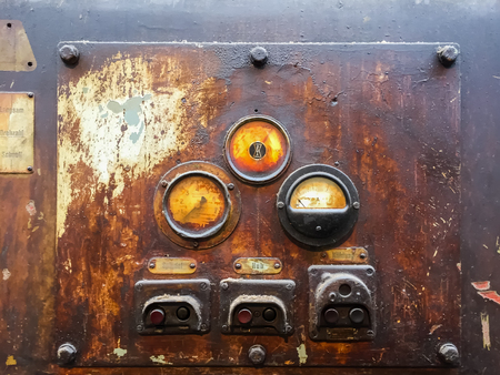 Old, rusty instrument panel of industrial machinery.