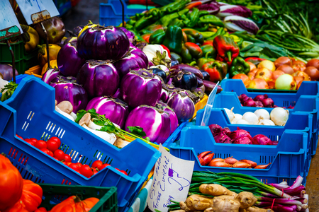 Vegetables in the display of a market stall. Stock Photo