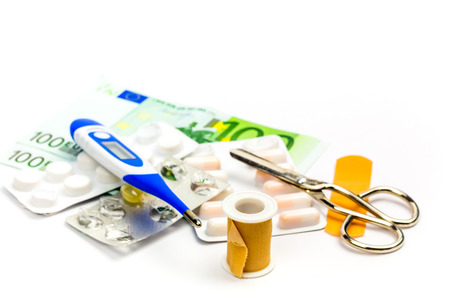 Pills and first aid equipment with bank note as a symbol of expensive medical care.