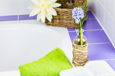 Purple hyacinth and a book at a bathtub. Stock Photo