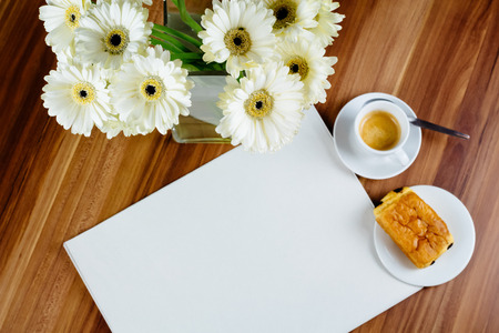 Blank newspaper, espresso and croissant.