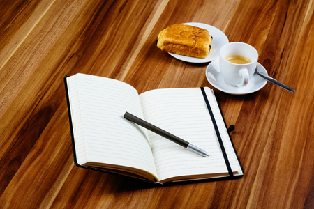 Notebook, pen, espresso and croissant. Stock Photo