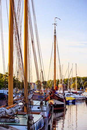 Old, historic sailboats and three-masters in a tranquil harbor in Holland during the sunset.
