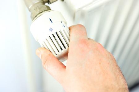 Hand turns down the heating. 写真素材