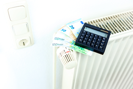 Money and calculator on a radiator symbolizes the expensive heating costs.