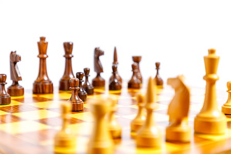 Wooden chess pieces on a chessboard with white background Stock fotó