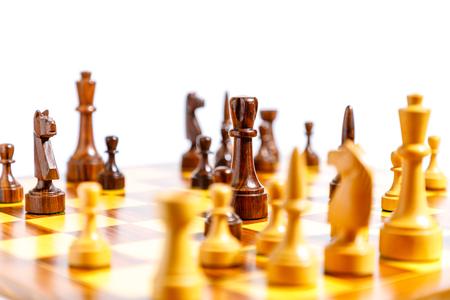 Pezzi degli scacchi di legno su una scacchiera con fondo bianco