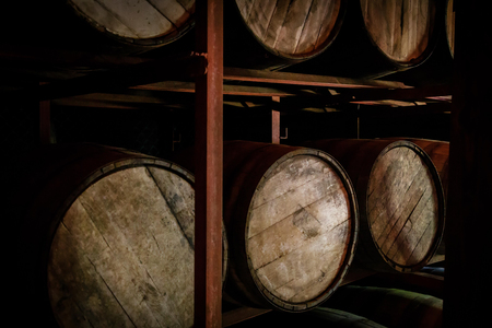 Rum or whiskey wooden barrels stacked in a warehouse