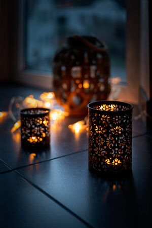 Light chain and candles create a cosy atmosphere. Romantic. Christmas Reklamní fotografie