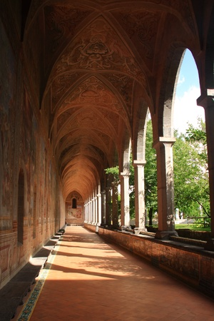 A long cloister in a catholic cathedral with a series of columns