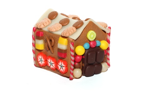 A handmade fimo marzipan house, with cookies, candies, fruits and flowers