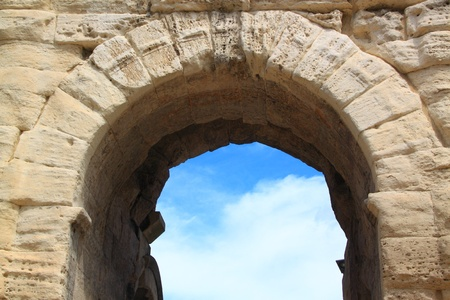 An ancient Roman arch of travertine on a background of a blue sky with clouds