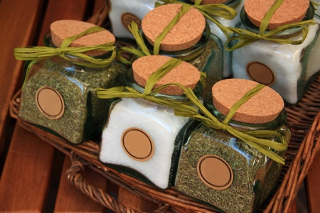 A wicker basket with jars containing salt and spices, closed with cork plugs and green ribbons photo