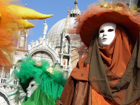 Colorful carnival masks in Venice. On the background the Saint Marks Basilica