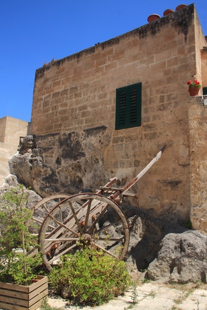Old wooden cart near the wall of bricks of a simple building, with a blue sky on the background Stock Photo - 12227878