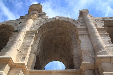 An ancient Roman arch of travertine on a background of a blue sky with clouds photo