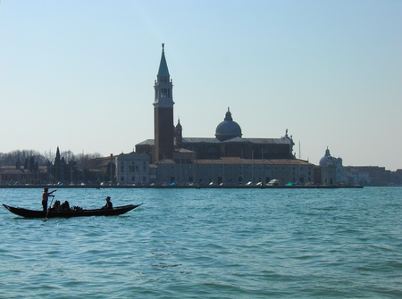 A gondolier standing on a gondola is carrying tourists in front of San Marco, Venice photo