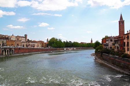 View of the Adige River in Verona, Italy. On the right the high tower of Santa Anastasia Church Stock Photo