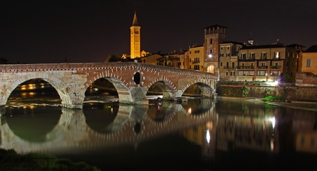 Night view of Old Bridge in Verona, reflected on the Adige river. On the background the high tower of Santa Anastasia Church, Verona Italy