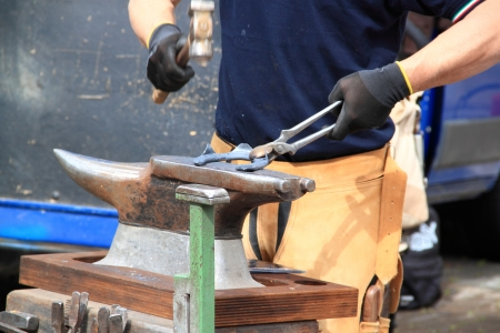 A farrier is making a horseshoe hitting with a hammer on the anvil Stock Photo