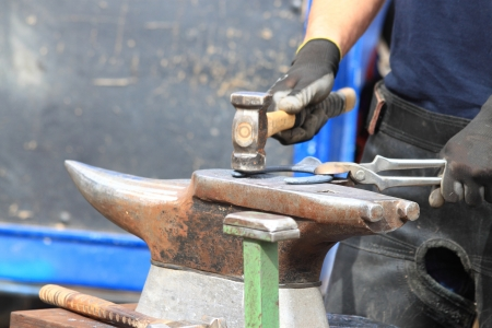A farrier is making a horseshoe hitting with a hammer on the anvil photo