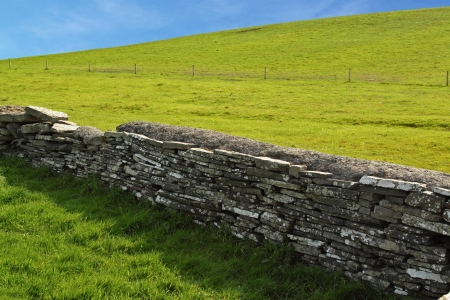 A wall of division between two green pastures, Ireland