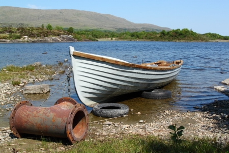 shallop: Old boat with a strange anchor, in a quiet lake in Ireland