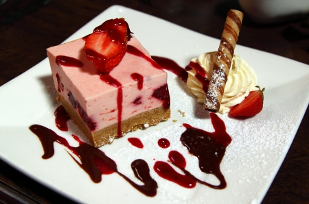 A delicious cheesecake with strawberries and cream photo
