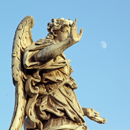 A marble statue of an Angel near Saint Angel Bridge in Rome, with a pale moon in the sky Stock Photo - 16900612