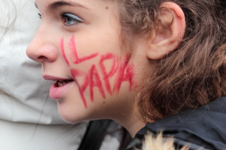 Young italian faithful with The Pope written on the cheek is waiting in St. Peter Square before the first Angelus of Pope Francis I Editorial