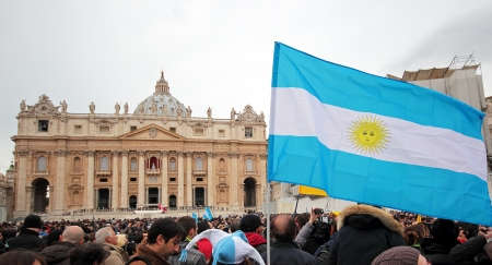 argentina flag: The crowd is waiting in St. Peter Square before the first Angelus prayer of Pope Francis I. A flag of Argentina in foreground.