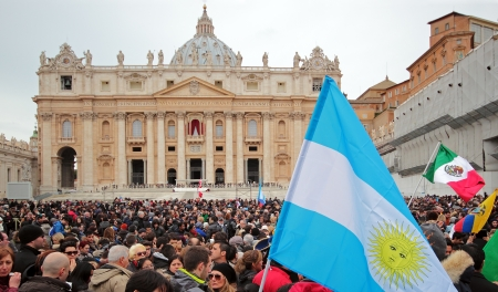 The crowd is waiting in St. Peter Square before the first Angelus prayer of Pope Francis I. A flag of Argentina in foreground.