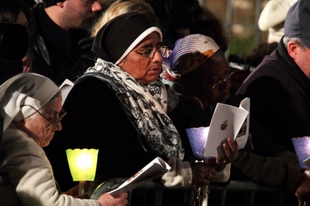 chaired: 29th March 2013, Colosseum Square, Rome: Women are reading the booklet of prayers during the Stations of the Cross chaired by the Pope Francis I around the coliseum on Good Friday. Candles are lit. Editorial