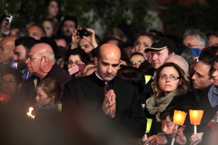 chaired: 29th March 2013, Colosseum Square, Rome: A praying prelate is walking through the crowd during the Stations of the Cross chaired by the Pope Francis I around the coliseum on Good Friday. Candles are lit.
