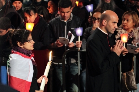 chaired: 29th March 2013, Colosseum Square, Rome: A praying prelate and a woman with a big candle are walking through the crowd during the Stations of the Cross chaired by the Pope Francis I around the coliseum on Good Friday. Candles are lit.