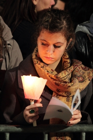chaired: 29th March 2013, Colosseum Square, Rome: A girl is reading the booklet of prayers, during for the Stations of the Cross chaired by the Pope Francis I around the coliseum on Good Friday.