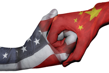 Diplomatic handshake between countries: flags of United States and China overprinted the two hands