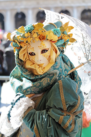 concealed: A woman with large eyes and an embroidered umbrella concealed by a mask exhibited during the traditional Carnival of Venice, Italy  2014 edition  Stock Photo