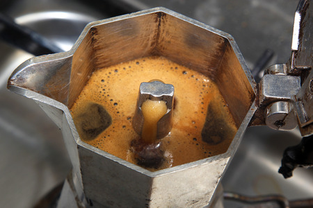 A metal coffeepot brewing Italian espresso coffee Stock Photo