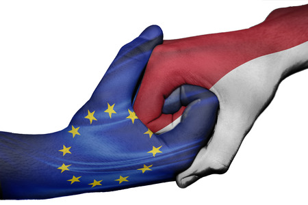 Diplomatic handshake between countries: flags of European Union and Indonesia overprinted the two hands
