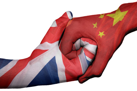 Diplomatic handshake between countries: flags of United Kingdom and China overprinted the two hands