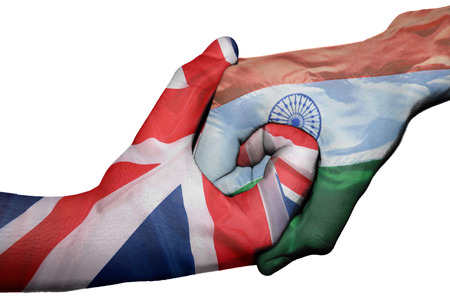 Diplomatic handshake between countries: flags of United Kingdom and India overprinted the two hands