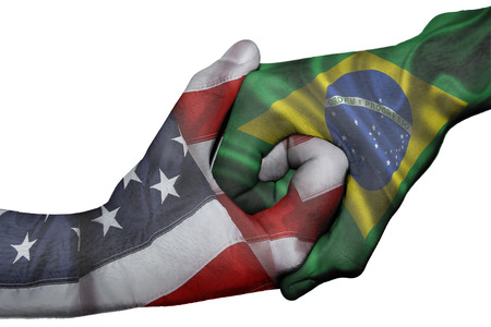 Diplomatic handshake between countries: flags of United States and Brazil overprinted the two hands