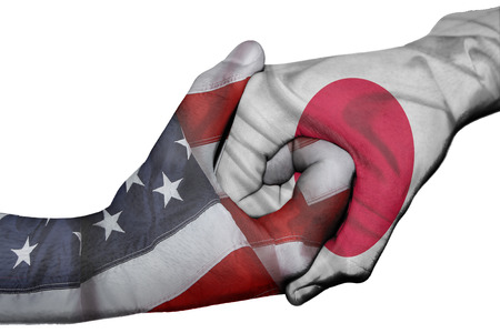 Diplomatic handshake between countries: flags of United States and Japan overprinted the two hands
