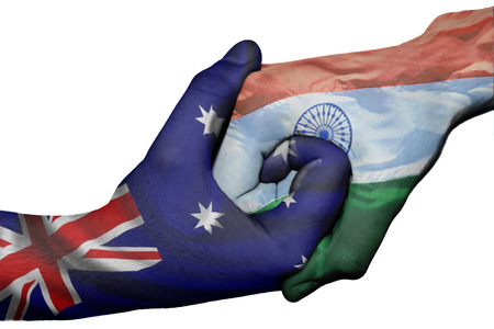 Diplomatic handshake between countries: flags of Australia and India overprinted the two hands